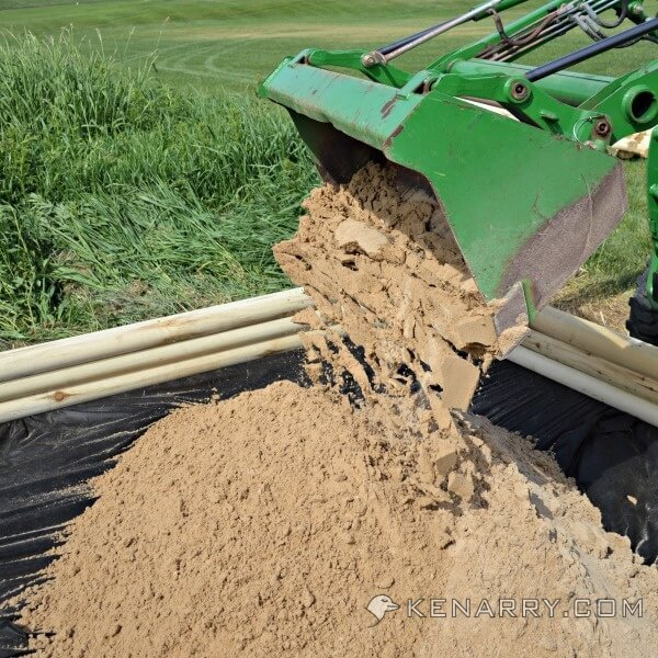 A tractor dumps sand into a new DIY wood sandbox