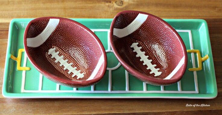 2 Football shaped bowls sitting in a football field shaped food platter.