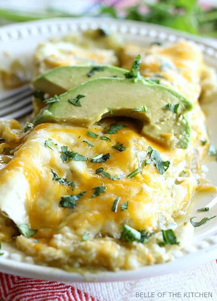 Creamy salsa verde chicken enchiladas with avocado slices on top