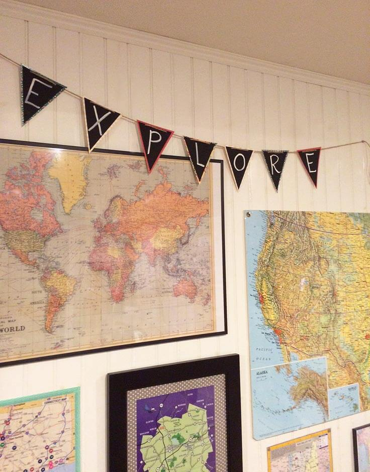 Create a gallery wall with maps and a handmade EXPLORE pennant banner.