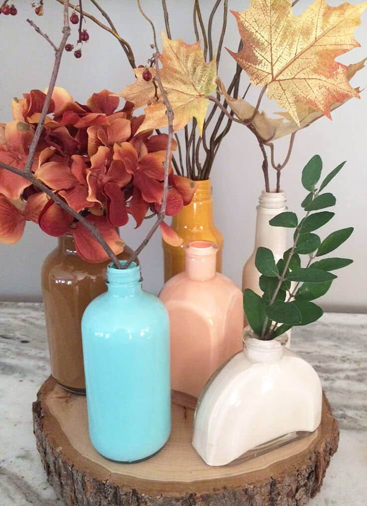 DIY painted glass jars with wood round for a beautiful fall centerpiece.