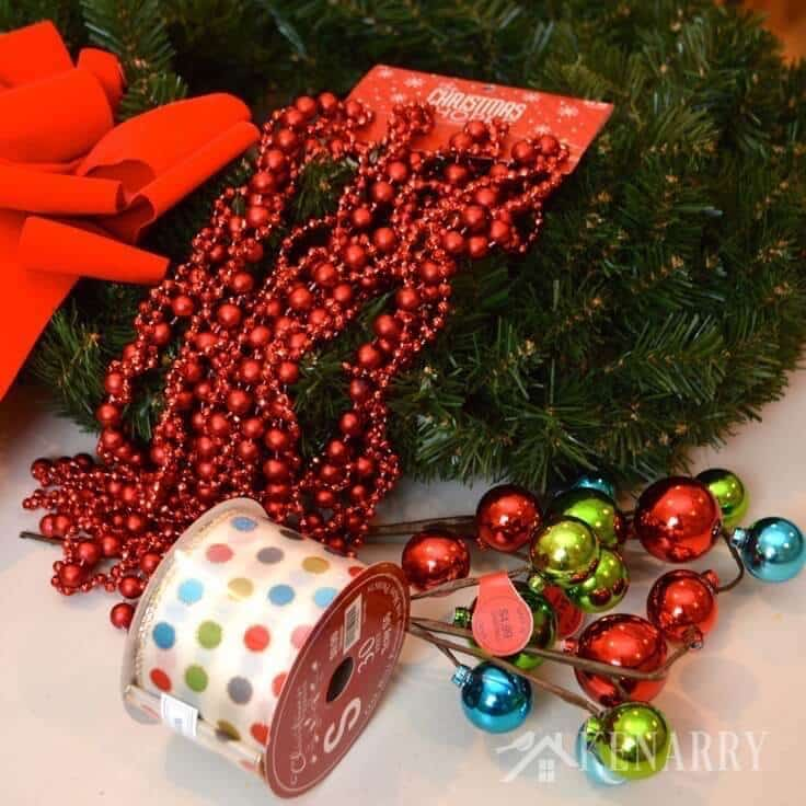 Love this idea to decorate an outdoor Christmas wreath with ribbon, beads and ornaments. Beautiful holiday home decor for your front door! - Kenarry.com