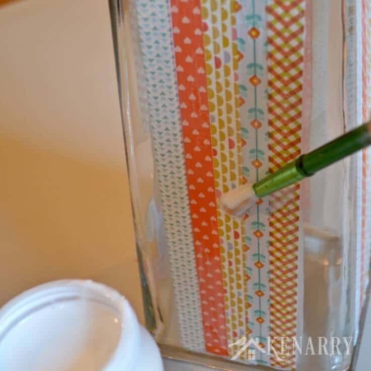 Using a paintbrush to apply Mod Podge to seal washi tape to a DIY Thanksgiving Vase