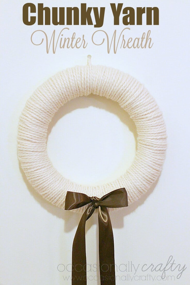 A chunky yarn winter wreath with a shiny brown bow.