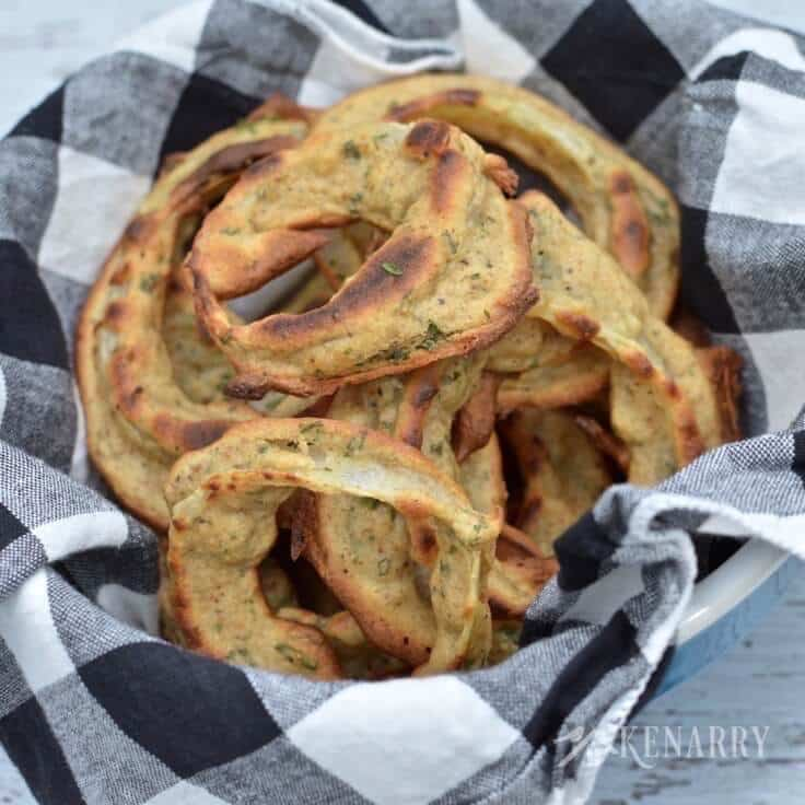 Homemade baked onion rings in a basket.