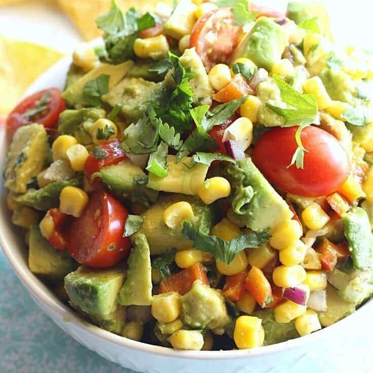 A closeup of corn avocado salsa with cilantro