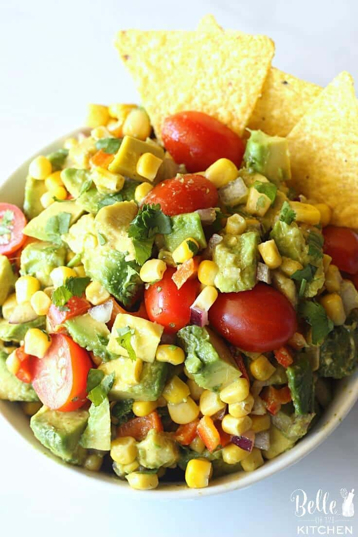 a bowl of  corn and avocado salsa served with tortilla chips