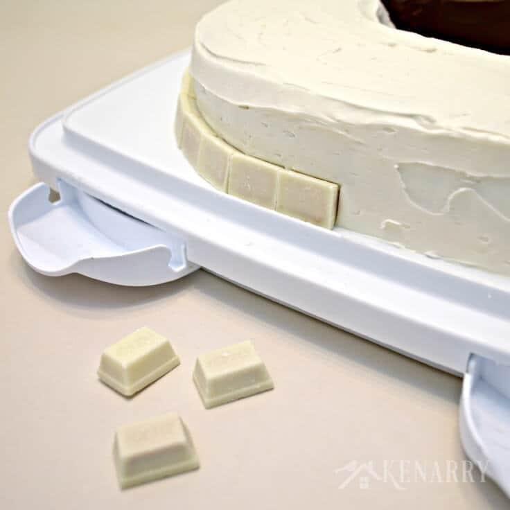 Putting white Kit-Kats around the vanilla side of the birthday cake.
