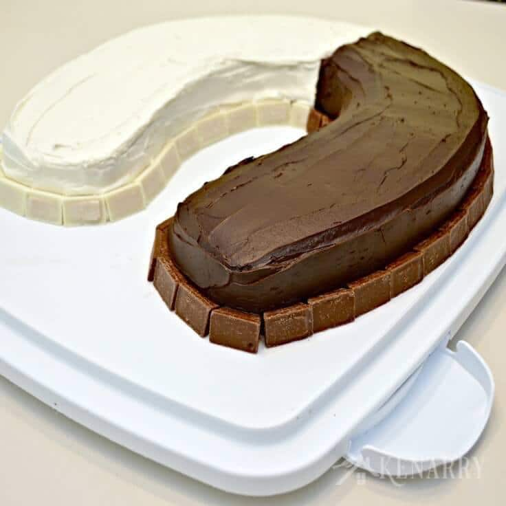 A u-shaped birthday cake that is half vanilla and half chocolate