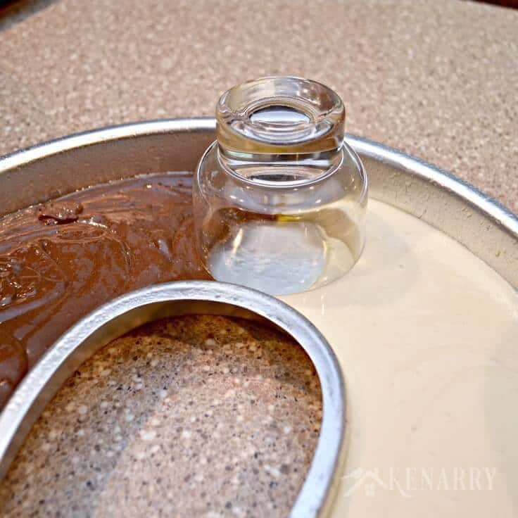 A glass cup separating the chocolate and vanilla cake batter