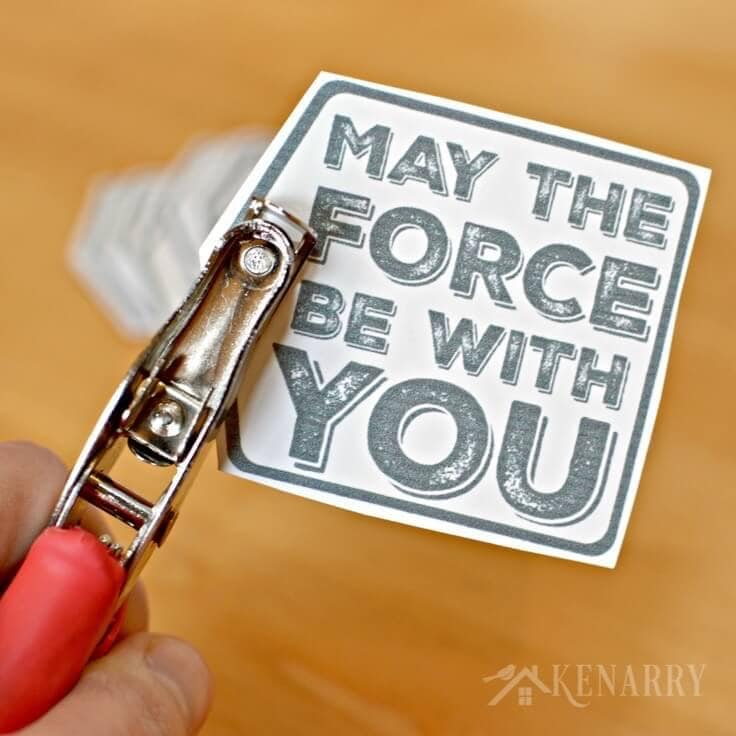 Using a paper hole puncher on the Star Wars gift tag that says May the Force Be With You.