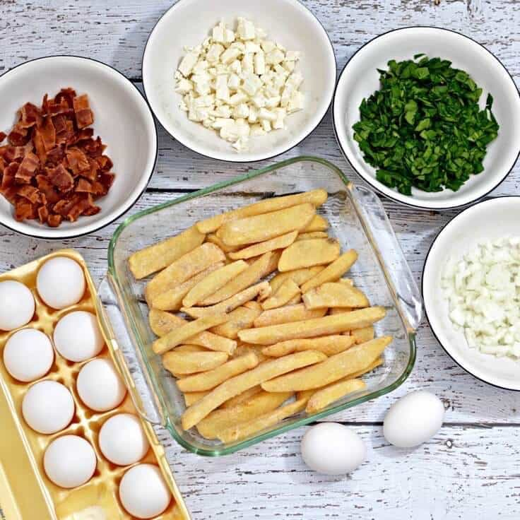 Ingredients for breakfast casserole - eggs, bacon, feta cheese, spinach, onion, french fries