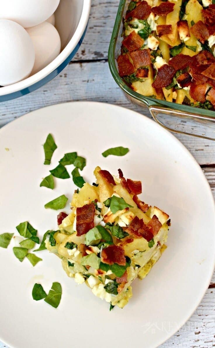Bacon, spinach and feta breakfast casserole served on a plate with the baking dish next to it