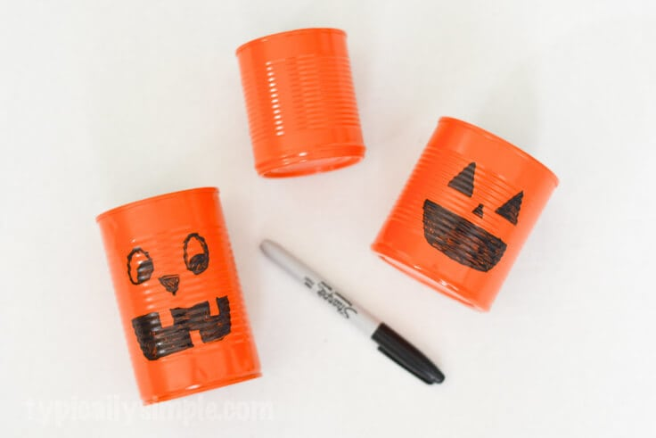 Using a black permanent marker to draw pumpkin faces on orange-painted tin cans.