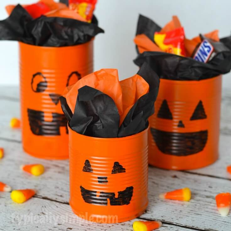 A close up of tin cans painted to look like halloween pumpkins.