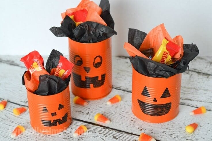 3 tin cans painted orange with jack o lantern faces and filled with candy.