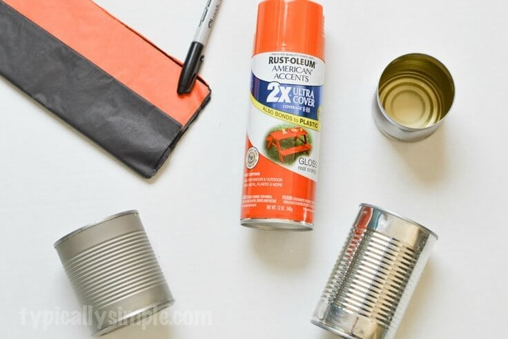 The supplies to make tin cans that look like pumpkins - empty cans, spray paint, marker and tissue paper