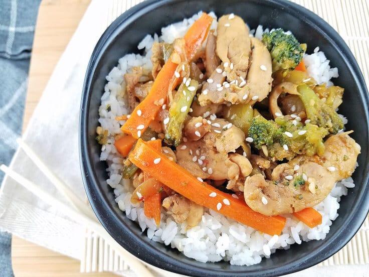 Homemade sesame chicken stir-fry on white rice in a black bowl.