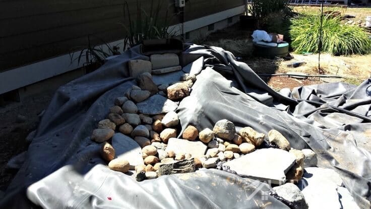 A tarp with rocks that will soon become a backyard waterfall