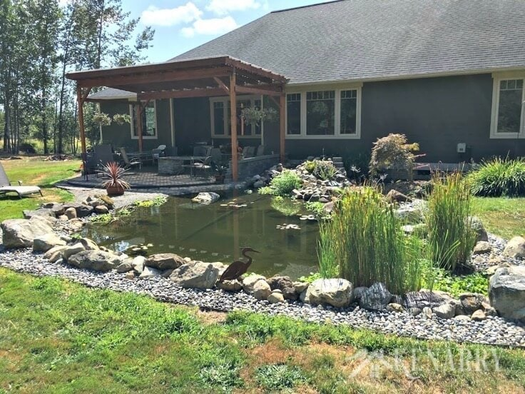 A backyard pond and covered patio