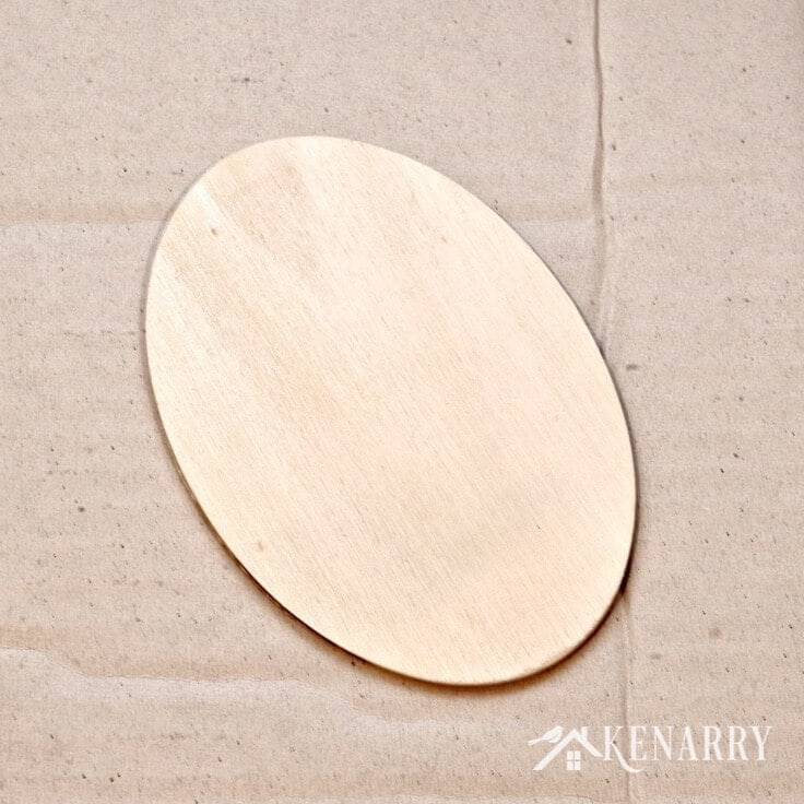 An unfinished oval wood sign