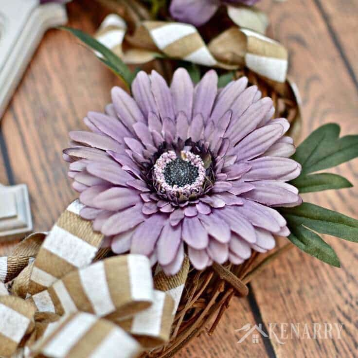 The purple flower attached to the grapevine wreath