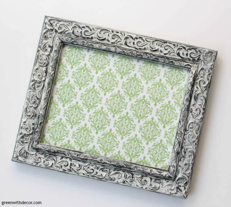 A picture frame with green-printed scrapbook paper inside it.