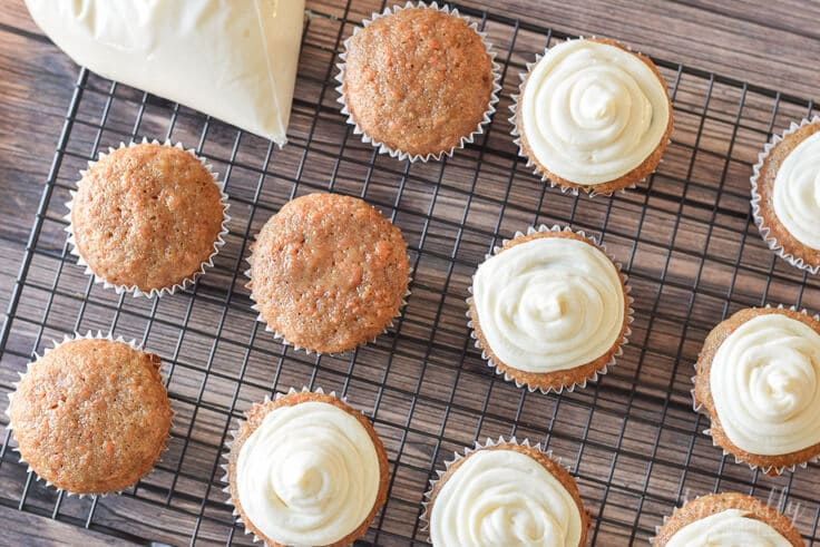 carrot cake cupcakes on a cooling rack being frosted with cream cheese frosting
