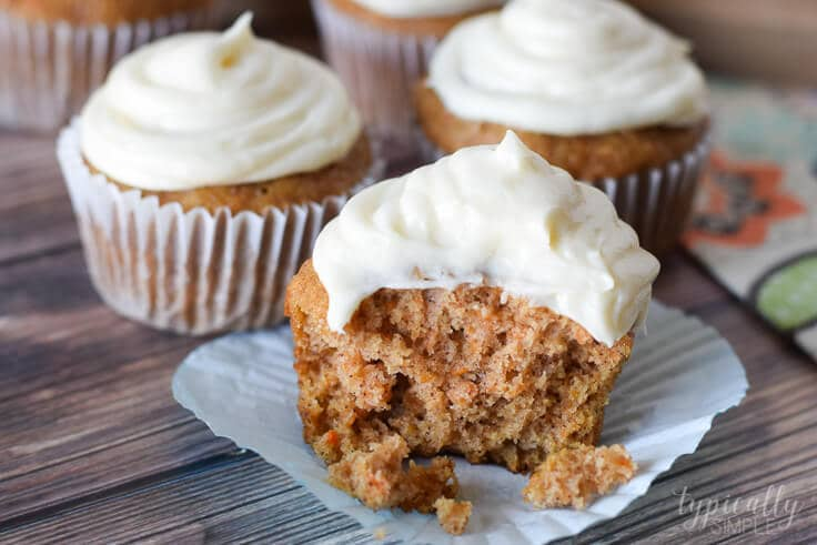 carrot cake cupcake with cream cheese frosting with a bite taken out of it