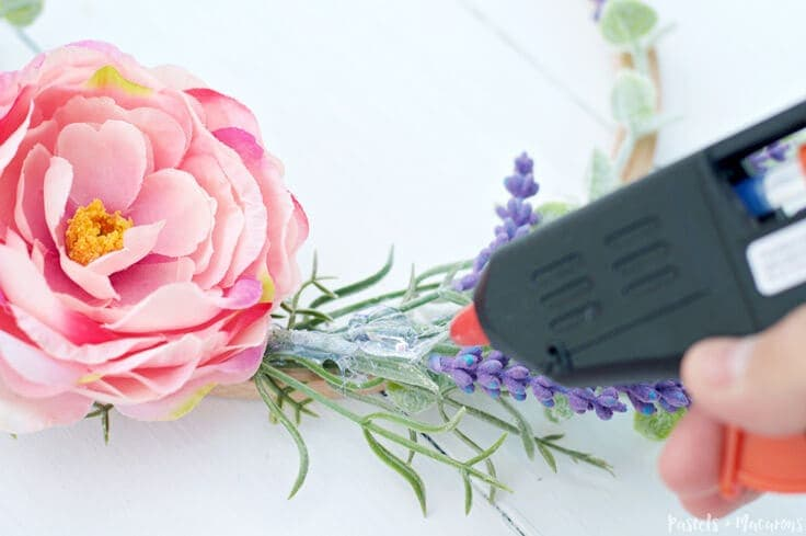 Hot glueing pink flowers to an embroidery hoop wreath
