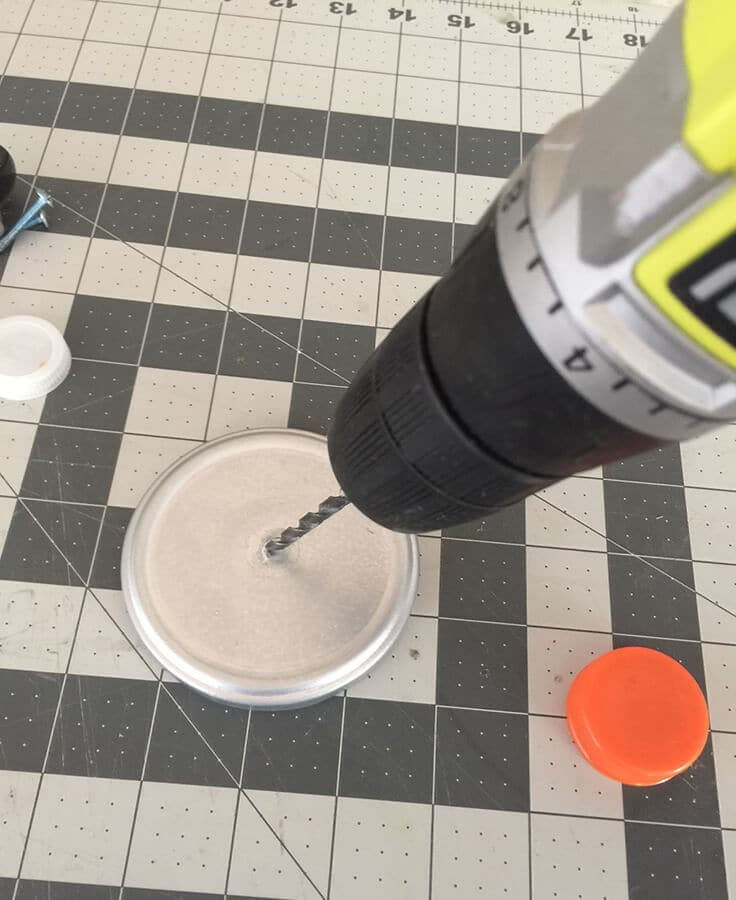 Using a drill to put a hole in a silver lid.