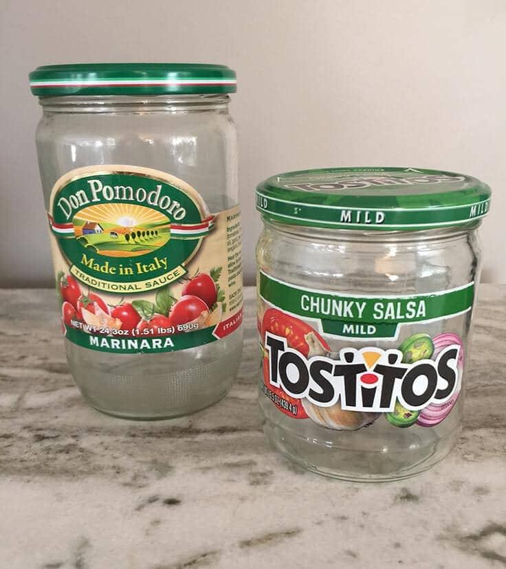 Cleaned and empty marinara glass jar and salsa glass jar. These can used to create bathroom storage jars.