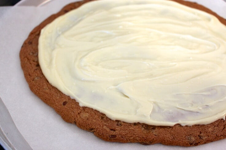 a pizza sized chocolate chip cookie with cream cheese frosting on top