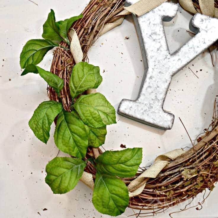 With a large industrial metal monogram and some rustic burlap ribbon this Spring Grapevine Wreath has that farmhouse style look that's so popular right now. This easy and beautiful craft idea will brighten up your front door all season long!