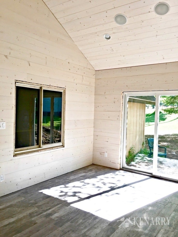 Porcelain tile looks like weathered wood. White washed pine plank walls installed in a sunroom as part of a cottage update. These shiplap walls give the room a rustic farmhouse style look.
