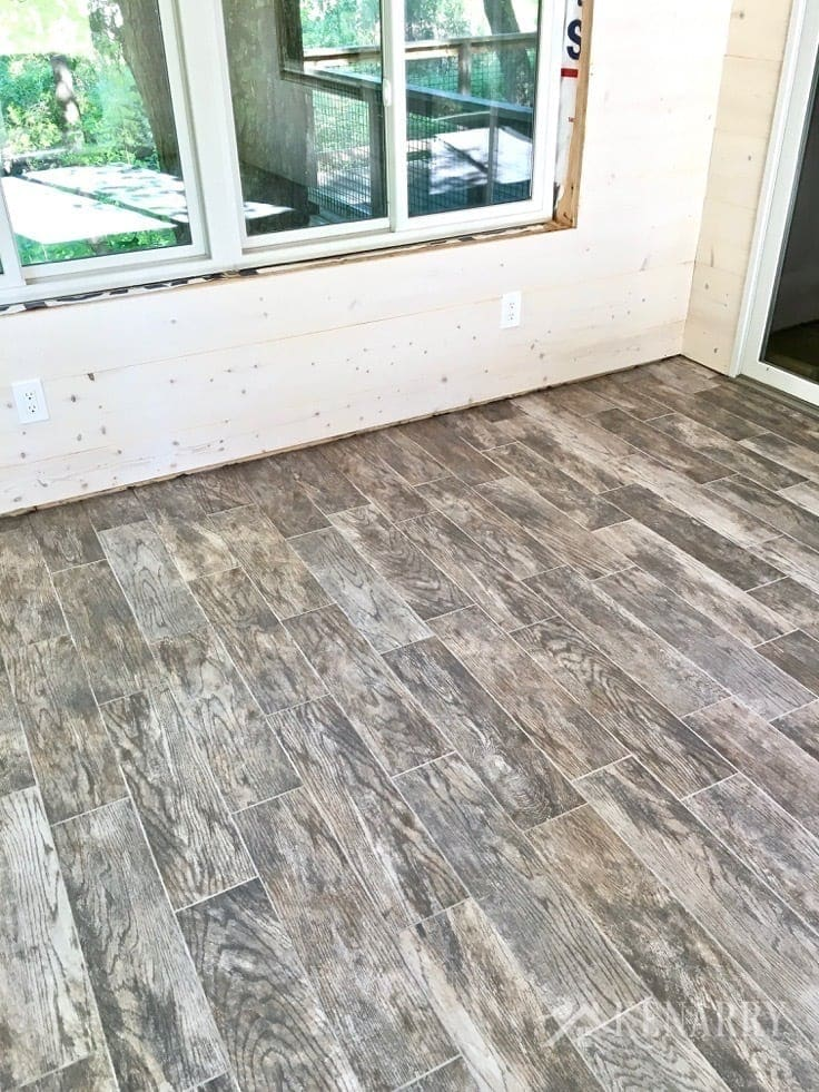 Marazzi Montagna Rustic Bay 6 in. x 24 in. Glazed Porcelain Floor Tile looks like weathered wood. White washed pine plank walls installed in a sunroom as part of a cottage update. These shiplap walls give the room a rustic farmhouse style look.