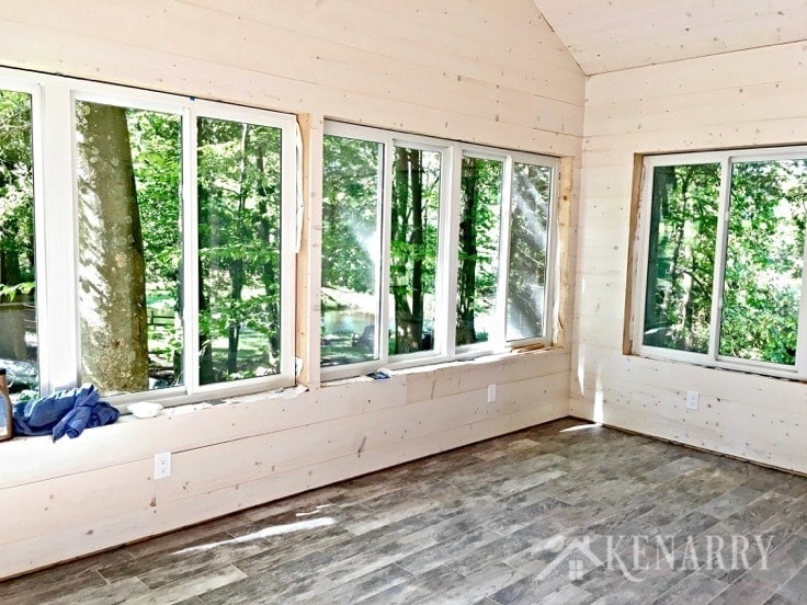 White washed pine plank walls installed in a sunroom as part of a cottage update. These shiplap walls give the room a rustic farmhouse style look. Porcelain tile looks like weathered wood.