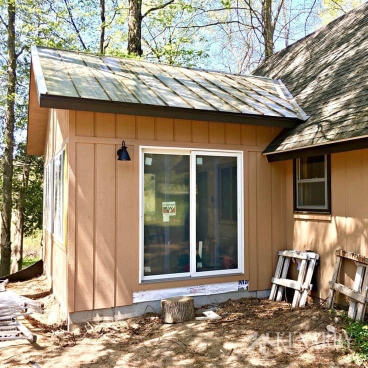 Dark brown metal roof and tan reverse board and batten exterior siding on the outside of this sunroom addition as part of a cottage update.