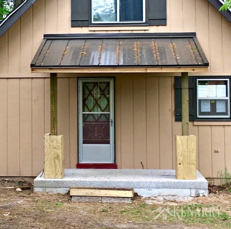 Dark brown metal roof and exposed aggregate concrete on this new front porch being built as part of a cottage update. The pillars will be covered with river rock.