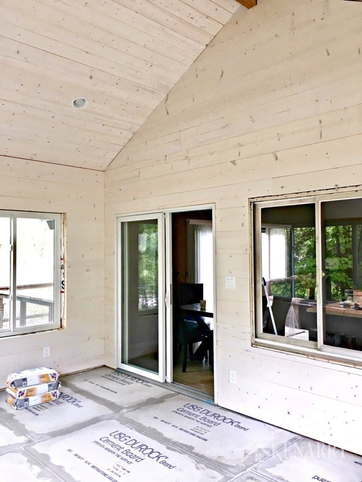 White washed pine plank walls installed in a sunroom as part of a cottage update. These shiplap walls give the room a rustic farmhouse style look. Cement board on the floor prepares the way for porcelain tile that looks like wood.