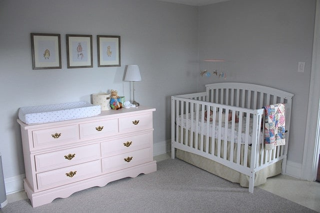 A pastel pink dresser and changing table next to a baby crib