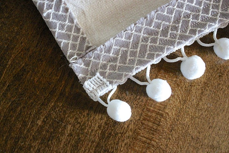 Fold over the extra pom pom trim and stitch it in place.