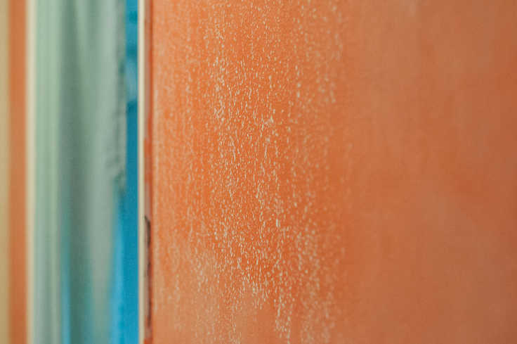 A close-up of an orange wall with white chalkboard paint on it.