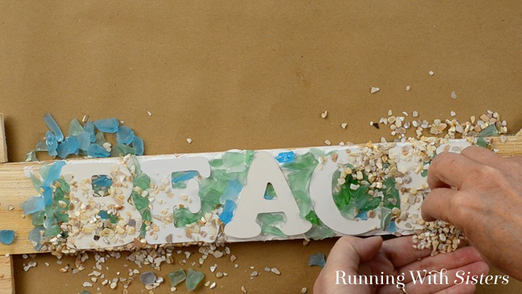 Make a beachy mosaic arrow sign without grout. We'll show you how to add sea glass, crushed shells, and sand to make an easy mosaic BEACH sign!