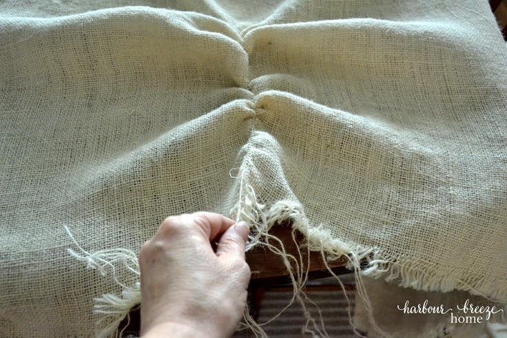 Pulling a strand of weave out of burlap so you get a straight line.