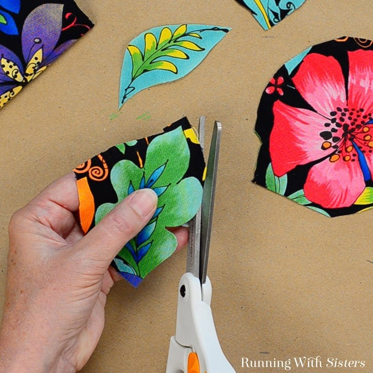 Cutting out floral fabric to put on a birdhouse