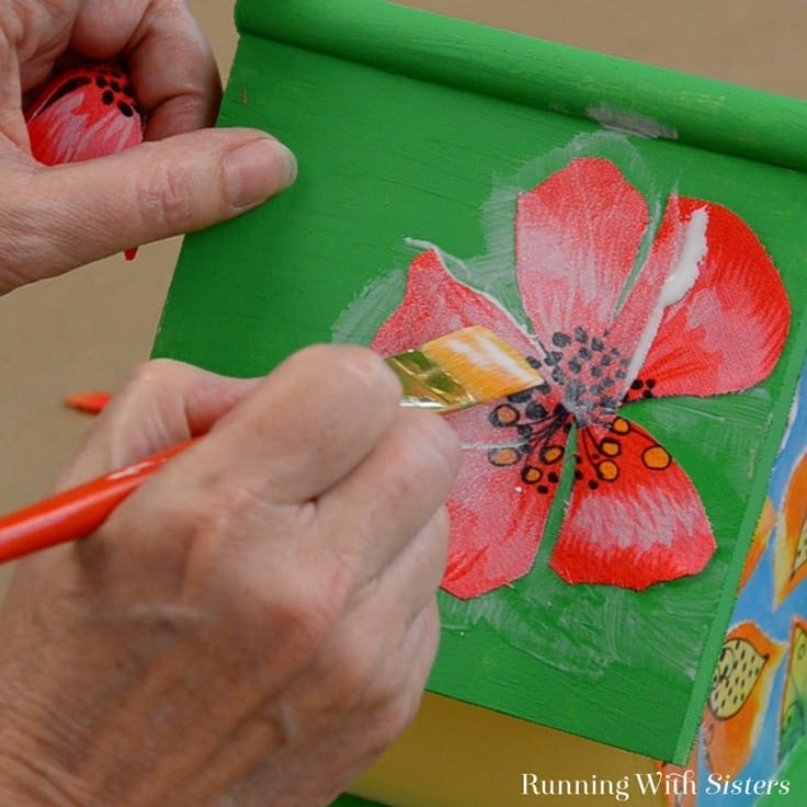 Gluing flowers on the roof of the birdhouse