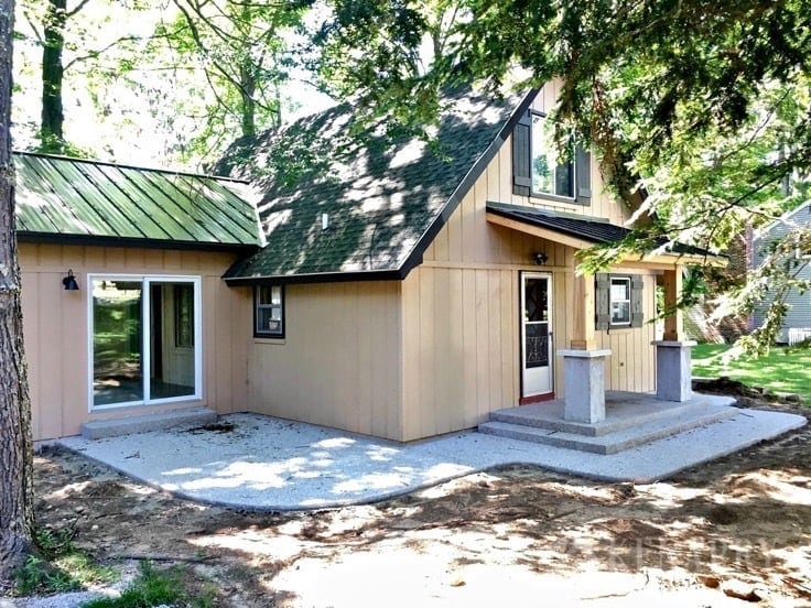 Craftsman style trim, a large exposed aggregate cement patio and low maintenance landscaping are all part of this big renovation project to add a sunroom and front porch to an A-frame cottage.