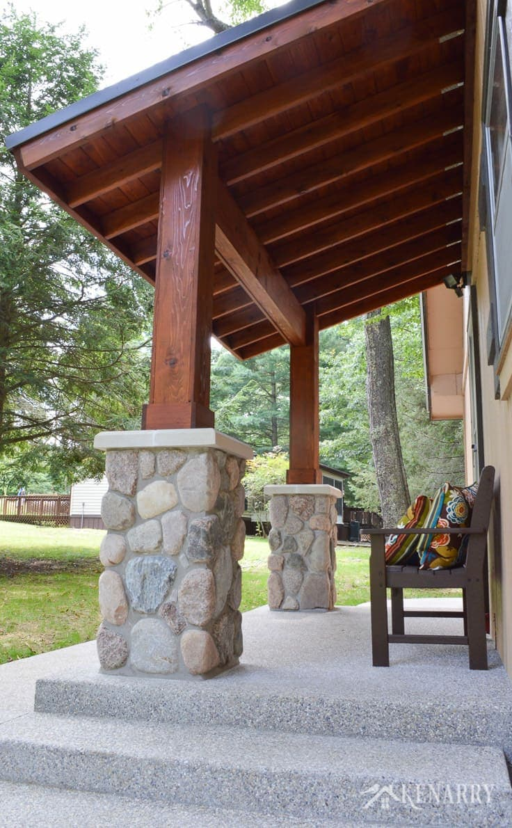 Cedar wood ceiling and river rock pillars add beautiful craftsman style to an A-frame cottage home | outdoor patio | mission style bench | home idea | exposed aggregate concrete