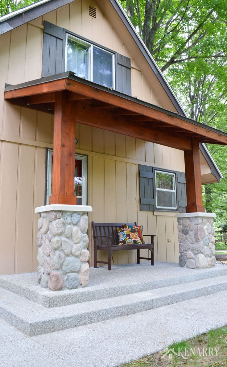 Exposed aggregate concrete steps and walkway surround this large craftsman style front porch created for an A-frame cottage home | river rock pillars | home idea | cedar posts | cedar ceiling | outdoor patio | mission style bench